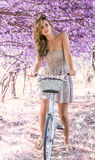 Young woman on bicycle in fantasy pink forest Stock Photo