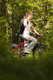 Young woman with bicycle in forest Royalty Free Stock Images