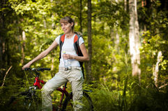 Young woman with bicycle in forest Royalty Free Stock Photo