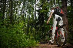 Young woman with bicycle in forest Royalty Free Stock Photos