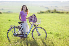 Young woman with a bicycle on green field on a sunny day Royalty Free Stock Photos