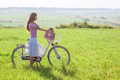 Young woman with a bicycle on green field on a sunny day Royalty Free Stock Photo
