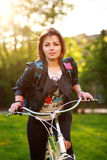 Young woman on bicycle in green park on sunset Royalty Free Stock Photos