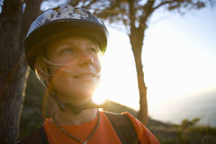 Young woman in bicycle helmet, smiling, close-up (lens flare) Royalty Free Stock Image