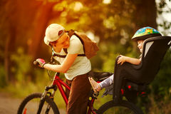 Young woman on a bicycle with little daughter  behind Royalty Free Stock Image