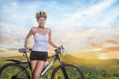 Young woman with bicycle on a mountain road Stock Photo