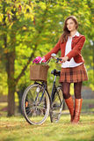 Young woman with a bicycle in a park Royalty Free Stock Photos