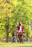 Young woman with bicycle in a park reading book Royalty Free Stock Photography