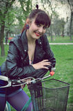 Young woman with bicycle in a park Royalty Free Stock Photography