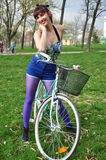 Young woman with bicycle in a park Stock Image
