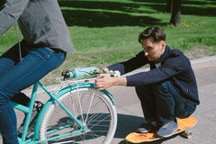 Young woman on bicycle pulling a man on a skateboard Stock Photography