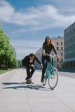Young woman on bicycle pulling a man on a skateboard Stock Photo