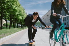 Young woman on bicycle pulling a man on a skateboard Stock Photos