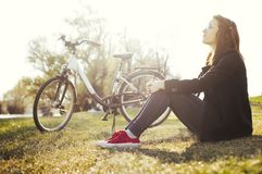 Young woman with bicycle relaxing sitting on grass in nature park royalty free stock photo