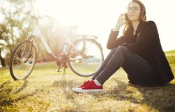 Young woman with bicycle relaxing sitting on grass using smart phone in park stock image