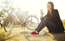 Young woman with bicycle relaxing sitting on grass using smart phone in park stock photo
