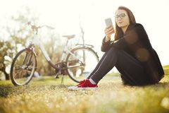 Young woman with bicycle relaxing sitting on grass using smart phone in park royalty free stock photos