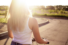 Young woman on bicycle in sunlight royalty free stock photo