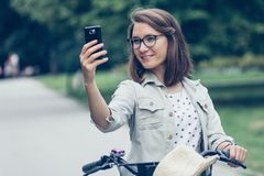 Young woman on bicycle taking selfie in park Stock Image