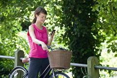 A young woman on a bicycle using a mobile phone Stock Images