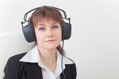 Young woman with big ear-phones on head Royalty Free Stock Photography