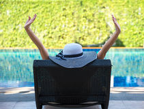 Young woman in big hat relaxing on the swimming pool, Stock Photo