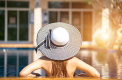 Young woman in big hat relaxing on the swimming pool, Royalty Free Stock Photo