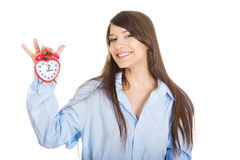 Young woman in big shirt holding alarm clock. Stock Image