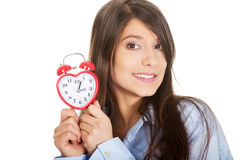 Young woman in big shirt holding alarm clock. Royalty Free Stock Images