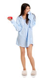 Young woman in big shirt holding alarm clock. Stock Images