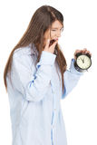Young woman in big shirt holding alarm clock. Stock Photography