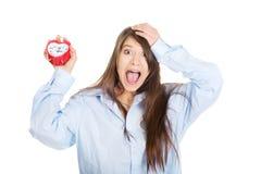 Young woman in big shirt holding alarm clock. Stock Photos
