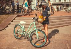 Young woman with big summer hat and vintage bicycle waiting for start of the festival Retro Cruise Stock Photo