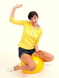 Young woman with big, yellow ball Stock Images