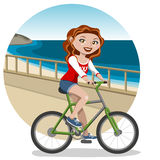 Young woman on bike. Lovely girl walking by the side of the beach by bike Royalty Free Stock Image