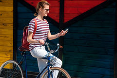 Young woman with a bike checking her phone Royalty Free Stock Photos