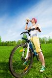 Young woman on a bike drinking water Royalty Free Stock Image
