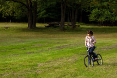 Young woman on bike in forest glade Royalty Free Stock Images