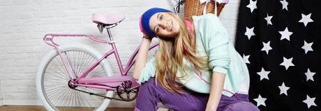 Young woman with bike at home Stock Photo