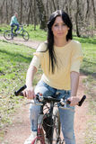Young woman on bike outdoors Stock Image