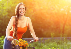 Young woman and bike. Young woman with a bike in a summer park. Active people. Outdoors Stock Photography