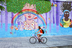 Young woman biking along colorful wall in Montevideo, Uruguay Royalty Free Stock Photography