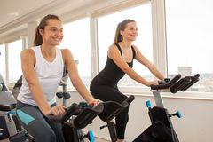 Young woman biking in the gym, exercising legs doing cardio wor stock image