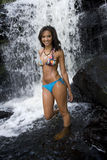 Young Woman in Bikini. Lovely young hispanic African American woman smiles in front of a water fall stock photo