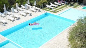 Young woman in bikini air mattress in the big swimming pool. Young woman relaxes on the air mattress in a swimming pool. Vacation concept stock footage