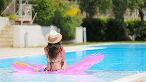 Young woman in bikini air mattress in the big swimming pool. Young woman in bikini is relaxing on an air mattress in a swimming pool. Vacation concept stock footage