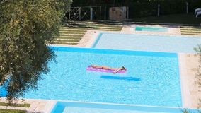 Young woman in bikini air mattress in the big swimming pool. Young woman in bikini is relaxing on an air mattress in a swimming pool. Vacation concept stock video footage