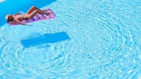 Young woman in bikini air mattress in the big swimming pool. Young woman in bikini is relaxing on an air mattress in a swimming pool. Vacation concept stock video