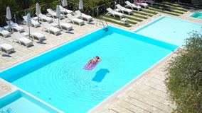 Young woman in bikini air mattress in the big swimming pool. Young woman is relaxing on an air mattress in a swimming pool from above view stock video