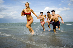 A young woman in a bikini being chased by three men Royalty Free Stock Photography